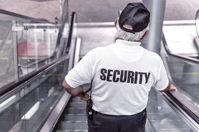 Un vigilante de seguridad baja por unas escaleras mecánicas.