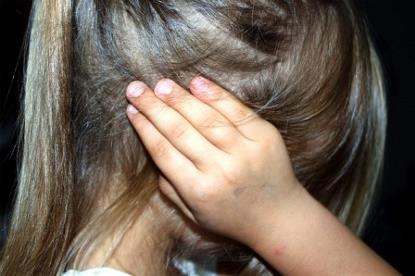 Una menor se tapa los oídos con las manos