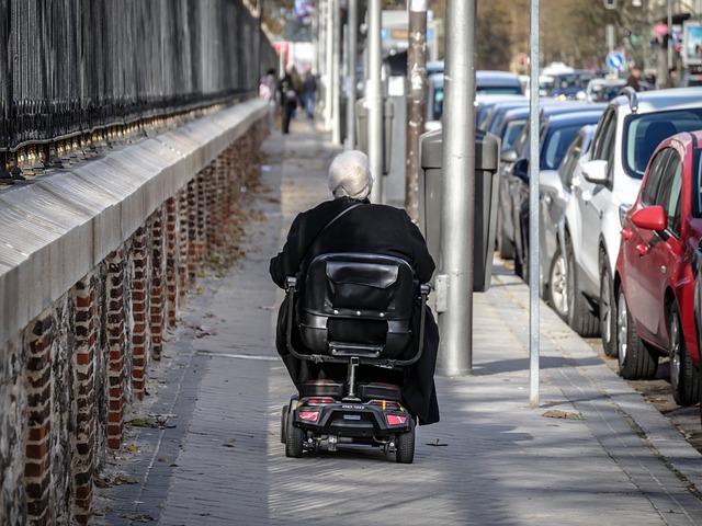 Una persona en un vehículo para movilidad reducida en una acera de ciudad