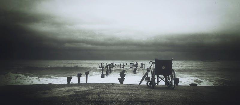 Silla de ruedas sobre una pasarela junto a una playa.