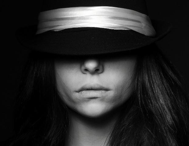 Mujer entre sombras con los ojos cubiertos por un sombrero