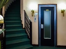 Entrada a un edificio con un ascensor y una escalera