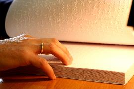 Una persona leyendo un libro en braille