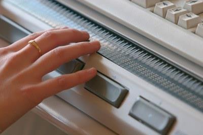Una persona leyendo en el ordenador en braille