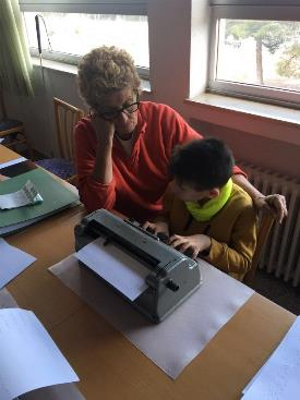 Una profesora enseña a escribir en braille a un niño