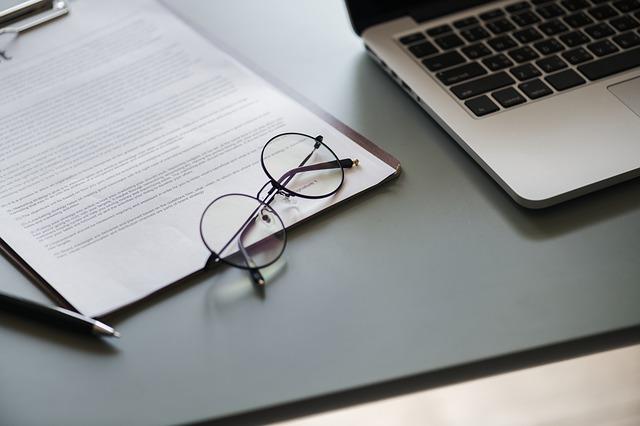 Papeles junto a un ordenador, unas gafas y un bolígrafo