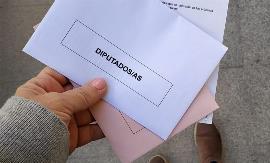 Unas manos llevan los sobres con las papeletas para las elecciones generales