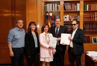 El presidente de las Cortes de Castilla-La Mancha, Jesús Fernández Vaquero, recibe un ejemplar de la Convención de manos de la presidenta del Cermi CLM, Cristina Gómez