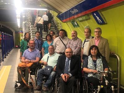 Foto de familia de la delegación de CERMI Madrid y CERMI Estatal en el andén de la estación de metro de Sevilla, en Madrid