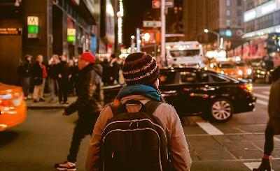 Calle de una ciudad con peatones y coches circulando