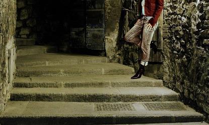 Piernas de una mujer en la calle, apoyada en una pared