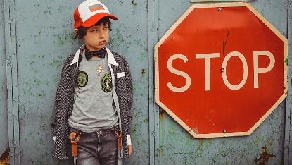 Imagen de un niño con una señal de stop al lado