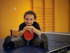 Joan Pahisa, con una raqueta sentado sobre una mesa de tenis de mesa