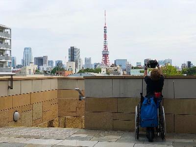 Joan Pahisa en Japón, haciendo una foto puesto en pie en su silla de ruedas