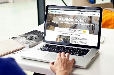Una persona con un ordenador navega por la web de Ilunion Hotels