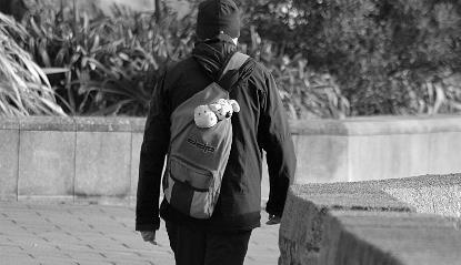 Joven de espaldas camina con mochila