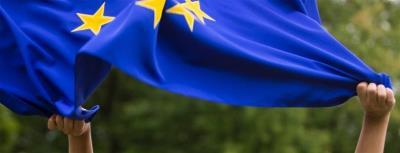 Unas manos ondean la bandera de la Unión Europea