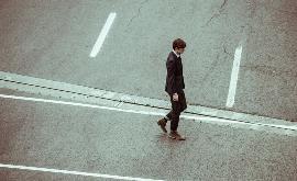 Un hombre trajeado paseo solo por una calle