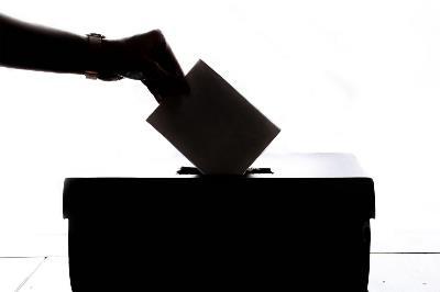 Dibujo de una persona depositando su voto en una urna.