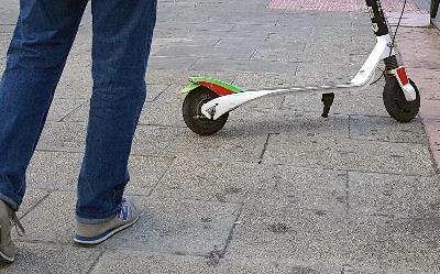 Imagen de unos pies y un patinete en mitad de la acera