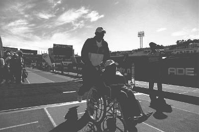 En un recinto deportivo, un hombre empuja una silla de ruedas de otra persona