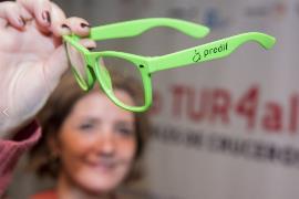 Gafas de ver, de color verde, con una inscripción de Predif y a través de las que se ve el cartel del congreso de cruceros