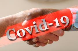 Manos que se estrechan y encima un cartel de COVID-19