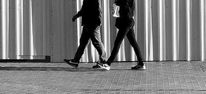 imagen recortada con las piernas de dos personas paseando