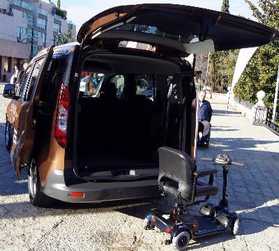 Imagen de una silla de una persona con movilidad reducida junto a un coche