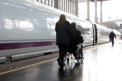 Una persona en silla de ruedas se dirige a un tren, acompañada por una ayudante