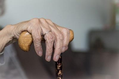 Una mano con la piel arrugada apoyada en un bastón