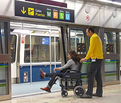 Una joven en silla de ruedas intenta acceder al metro, con la ayuda de un asistente