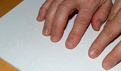 Manos de una persona con discapacidad visual leyendo un texto en braille