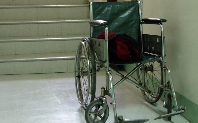 Silla de ruedas al pie de unas escaleras