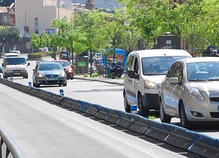 Varios vehículos circulan por una vía urbana