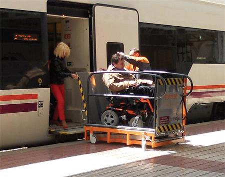 Acceso al tren de una persona en silla de ruedas mediante una plataforma elevadora y la ayuda del servicio de asistencia al viajero