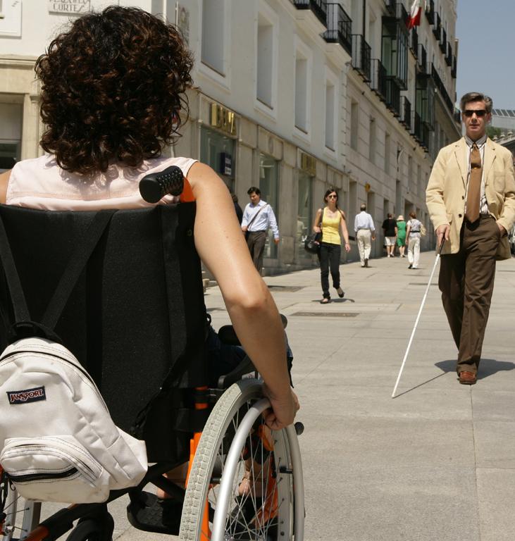 Un hombre ciego y una mujer en silla de ruedas en una calle de una ciudad