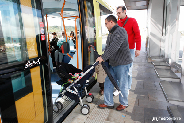 Usurio del tranvía de Tenerife entrando a un vagón con un carrito de bebés