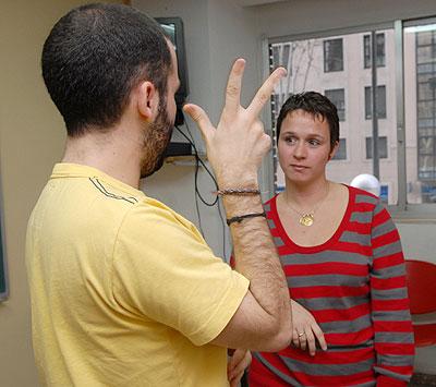 Un voluntario enseña lengua de signos a una persona con ceguera