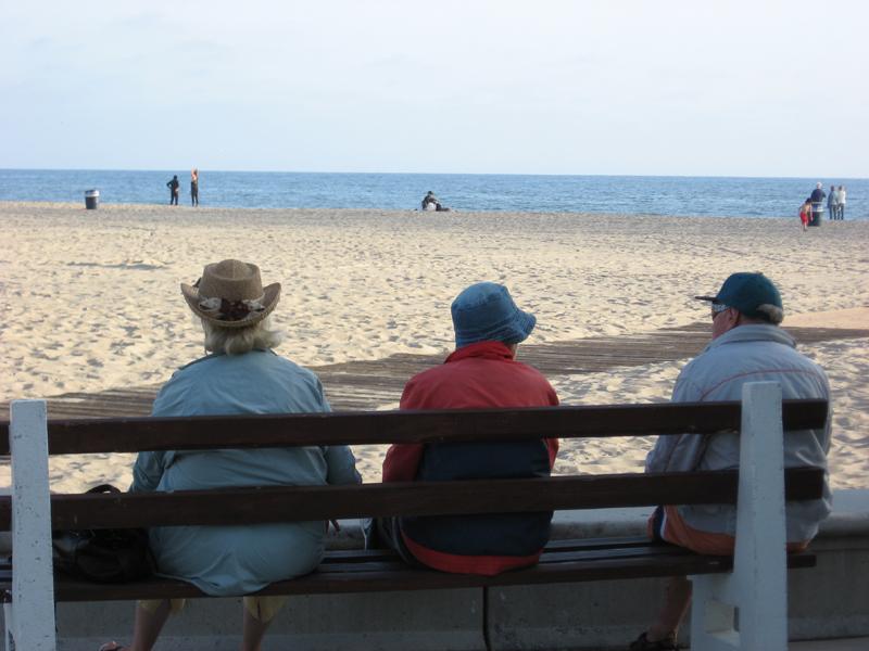 Personas mayores sentadas en un banco en la playa
